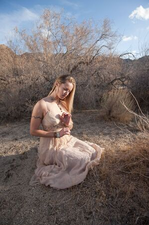 wicca: Young woman in a beautiful dress kneeling in a secluded desert landscape.