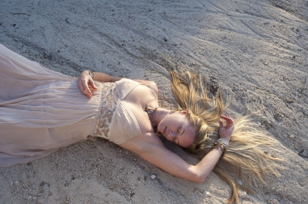 Woman lying in dry river run in a beautiful gown. Elise Kost jewelry.