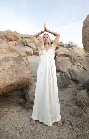 bridal gown: Young woman in white bridal gown in the desert with her hands in Temple Yoga Mudra.  Stock Photo