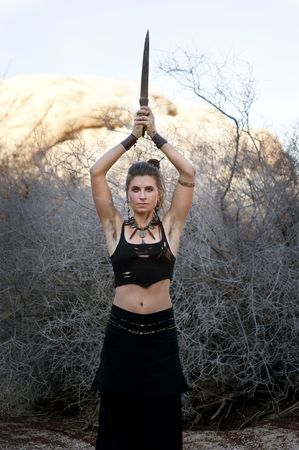 Woman in the modern tribal adornment style with raised dagger.