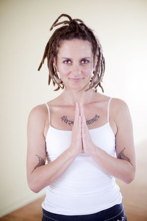 Portrait of a lovely unique woman with dreadlocks and Sankrit tattoo in prayer pose. Stock Photo - 6862784