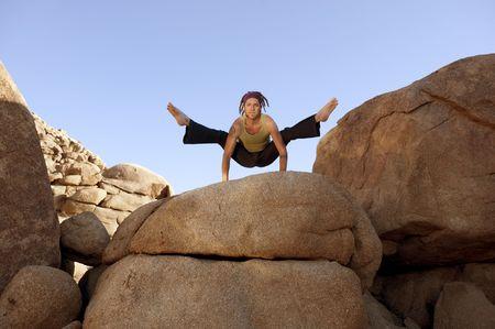 Free spirited man practicing hatha yoga posture titibasana on some giant rocks.  photo