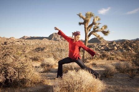 Yogi in the desert in an alternative warrior 2 posture.  photo