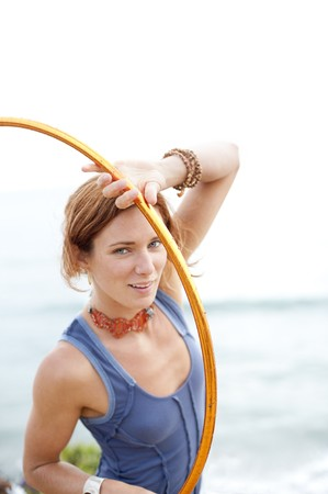 Portrait of a young woman near the beach with her hoop. photo