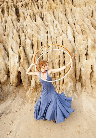 Hoop dancer next to a earthen formation.  photo
