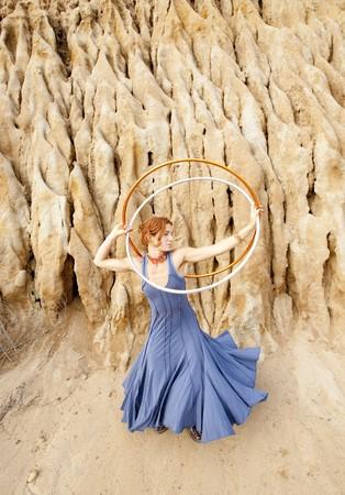 prana: Hoop dancer next to a earthen formation.