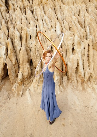 Woman in a blue dress with hoops in an atomic shape by an earthen structure.  Stock Photo