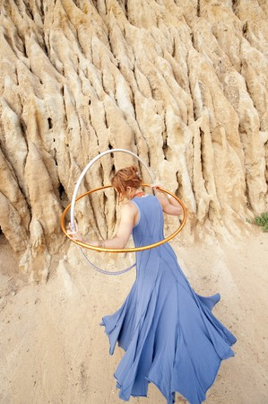 enso: The back of a woman in a blue dress holding hoops in an earthen landscape. Stock Photo