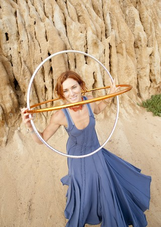 prana: Young woman with hoops smiling in front of an earthen structure.