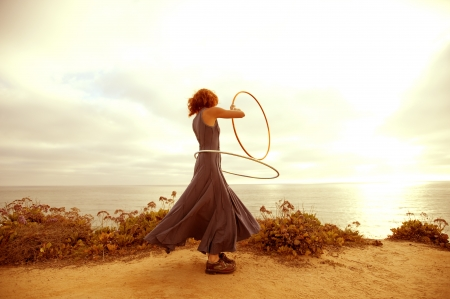 A woman hooping in the sunset.