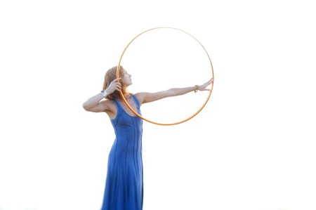 wholeness: Blurred Lensbaby image of woman holding a gold hoop like a bow, Lensbaby lenses are pruposefully soft focused images.  Stock Photo