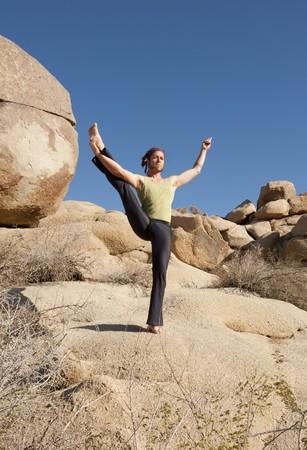 prana: Man in yoga standing balance Parsva Utthita Hasta Padangusthasana pose outdoors in the bolders. Stock Photo