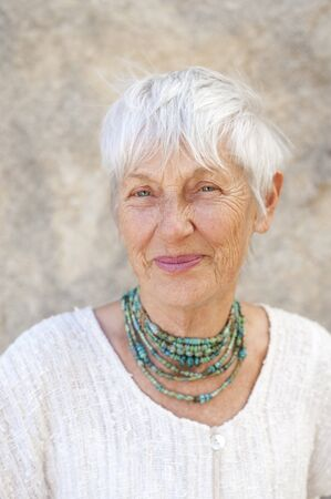 aging woman: Portrait of a lovely and graceful senior woman wearing jewelry