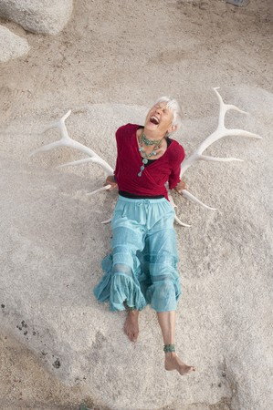 Portrait of a naturally wild and crazy senior woman laying in Elk antlers. Stock Photo - 7352132