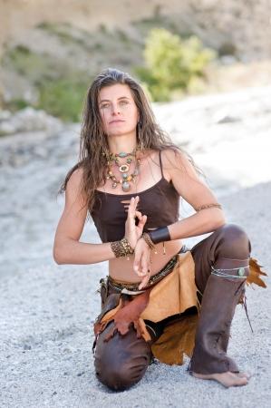 Woman coruching wearing artisan made leather pants and jewelry, Stock Photo - 8216471