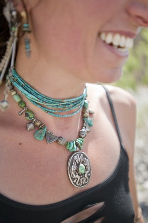 Close up of a dragon necklace worn by an anonymous smile.  photo