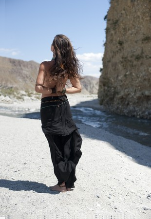 Beautiful young woman seen from the back standing near a desert river with her hands in a reverse yoga mudra.
