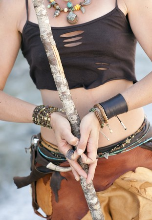 The hands and torso of an unseen woman wearing tribal adornment.  photo