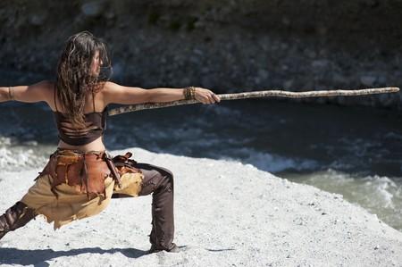 Vrouw in tribale stijl oefenen zelf verdediging met een longstick.