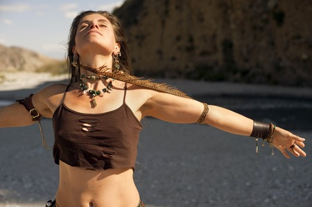 Woman with arm spread wide wearing a long feather earring near a desert river.