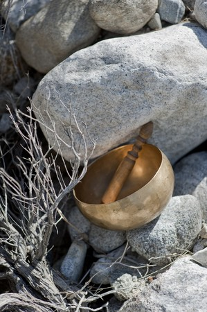 A tibetan singing bowl resting in desert rocks.  photo