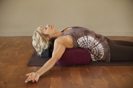 Frau mittleren Alters ruht auf einer Yoga-Nachläufer.