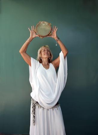 Woman in white raising a tamborine over her head.