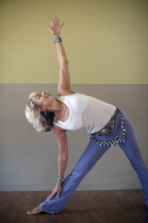Portrait of a woman in the yoga pose triangle indoors.  photo