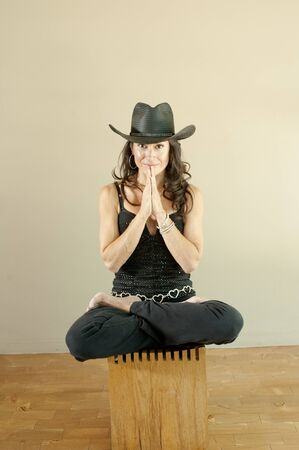 Portrait of woman in her 40s wearing a black cowbody hat sitting in lotus pose.  photo