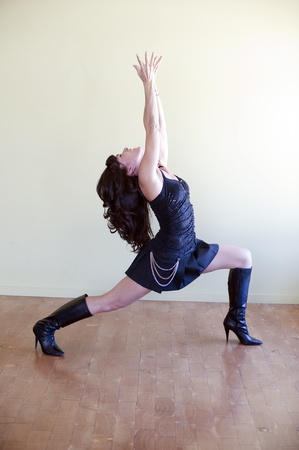 Tantric woman in yoga pose Warrior 1; Virabhadra,  while wearing high heeled boots. Stock Photo - 9189853