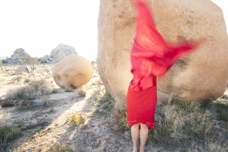 spirtual: Woman cloaked in red blur standing in a dramatic stone landscape