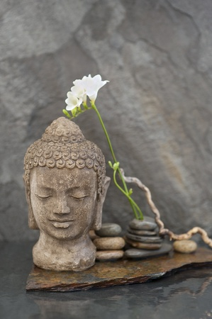 stone buddha: Stone Buddha head sculpture with flower and stones in water  Stock Photo