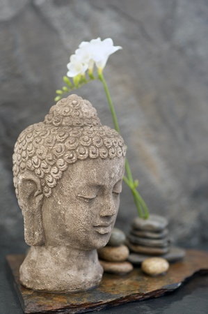 Stone Buddha head sculpture, stones, and flower in watery element