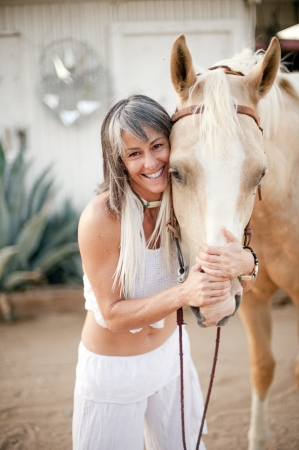 human kind: Beautiful fit aging smiling woman with her horse  Stock Photo