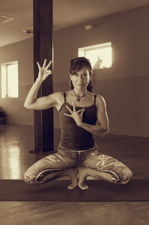 sutra: Woman in a toe squat yoga posture with a hand mudra near her heart.