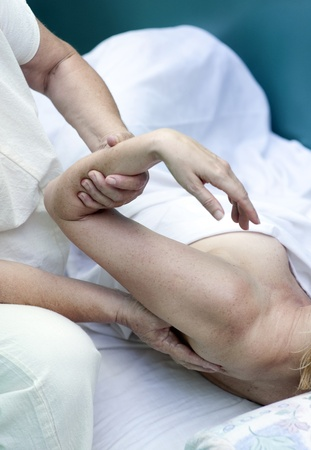 The hands of a bodyworker and her client as she works deep into the shoulder. Stock Photo - 15512627