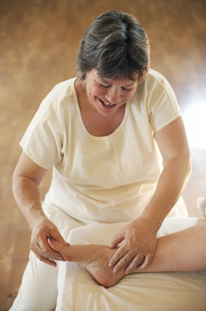 Mature body worker giving foot massage therapy.