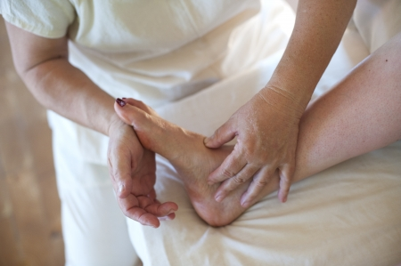 pain relief: A massage therapists hands working on her clients foot. Stock Photo