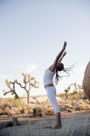 Woman in a natural environment opening her heart chakra up to the sky in a freeform yoga sun salute.  Stock Photo