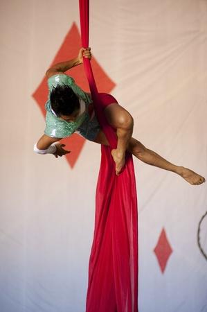 somatic: Graceful aerial acrobat hanging on silk scarves.