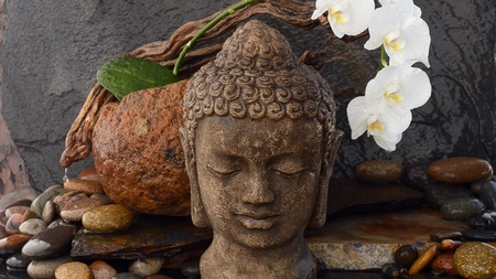 Stone Buddha head sculpture photographed in a zen fountain  Stock Photo