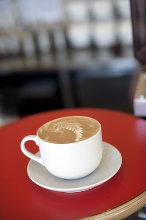 capacino: Fancy Cappuccino in a white cup ready for pick-up at the bar
