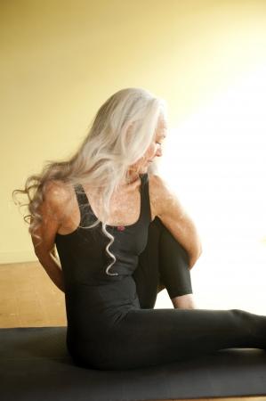 cabelo amarrado: Mulher madura em um yoga obrigado pose assentado