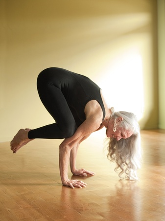 Mature woman in the yoga posture Bakasana or crow pose.