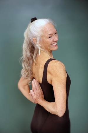 aging: Senior woman in the yoga pose reverse prayer.  Stock Photo