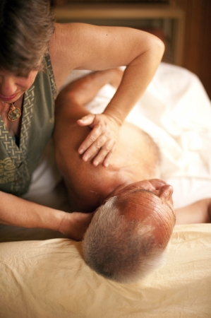 senior man on a neck pain: Bodyworker working on her senior client