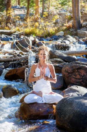 Smiling yoga woman sitting on a river boulder  photo