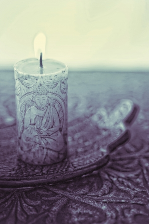 A lit buddha candle in a simple setting