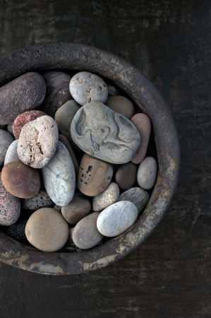 River stones collected in a rust bowl