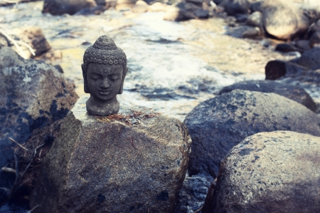 Buddha head on a river boulder  photo